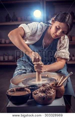 Beautiful Ceramist Woman Molding A Vase Of Clay On A Potters Wheel. Handcraft.