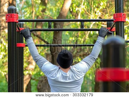 A Young Man Performs A Sports Exercise Pulling On The Simulator Crossbar. Outdoor Training Develops