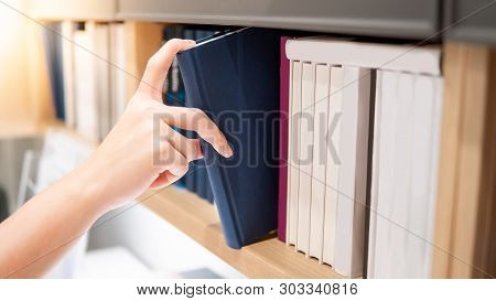 Male Hand Choosing And Picking Blue Book From Wooden Bookshelf In Public Library. Education Research