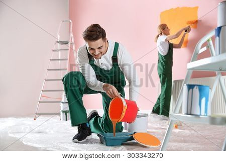 Professional Decorator With Bucket Of Paint Indoors. Home Repair Service