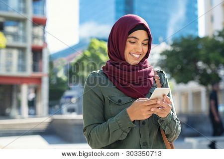 Pretty muslim woman using mobile phone outdoor. Arabic woman wearing hijab using smartphone on the street. Islamic girl texting a message phone in city centre.