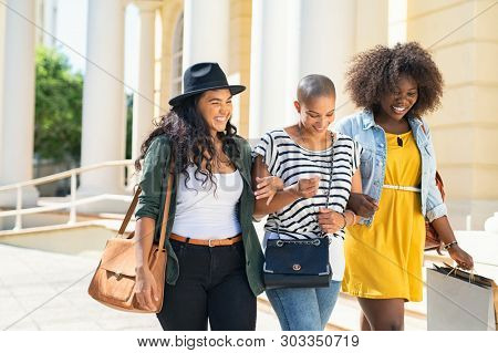 Group friends walking and holding shopping bags. Three happy young women walking in the city talking to each other while having fun. Multiethnic group of girls smiling with shopping bags outdoor.