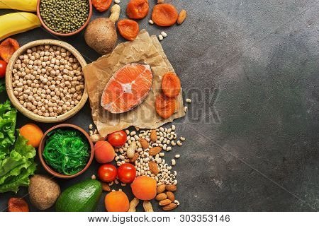 Foods Rich In Potassium, Salmon, Legumes, Vegetables, Fruits On A Dark Background. Healthy Food Conc