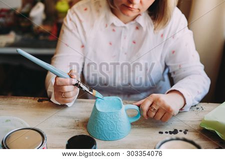 Woman Working In Her Pottery Studio. Ceramic Workshop. Paint On Clay Cup In The Pottery. Painting In