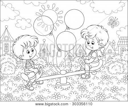 Little Children Playing On A Toy Seesaw On A Playground In A Park Of A Small Town On A Sunny Summer