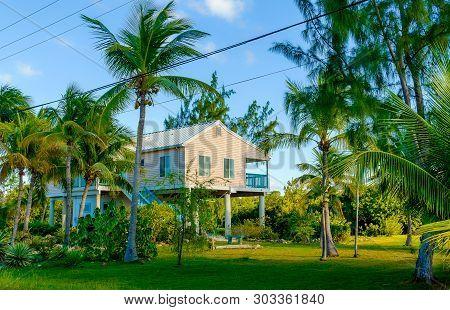 Little Cayman, Cayman Islands, Nov 2018, House On Stilts With A Lush Tropical Garden Around It