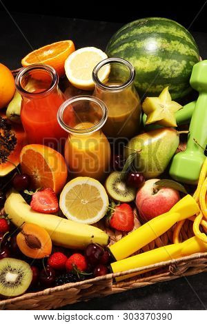 Healthy Lifestyle Concept. Healthy Fruits, Smoothies And Sport Fitness Equipment, Dumbbells And Jump