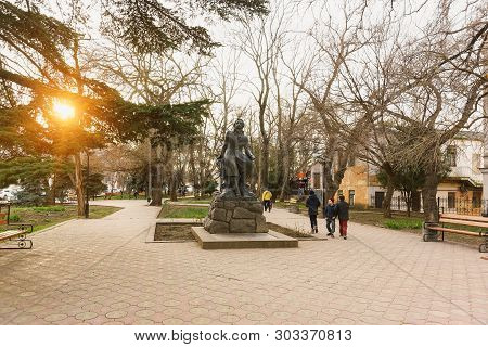 People In The Park Near The Monument To Alexander Pushkin. Bright Ray Of Sunset