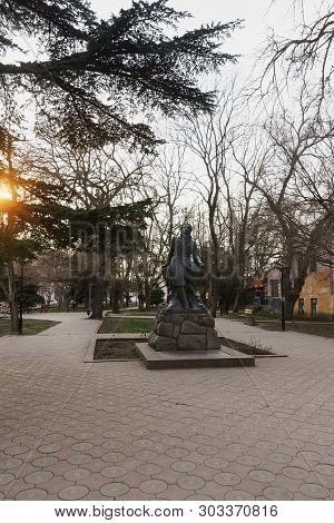 Monument To Alexander Pushkin In The City Square Of The Same Name. Bright Ray Of Sunset