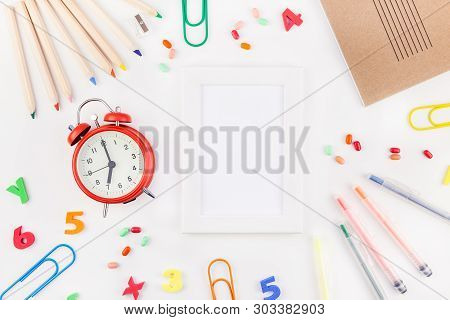 Creative Flat Lay Back To School Concept With Alarm Clock, Color School And Office Supplies On White