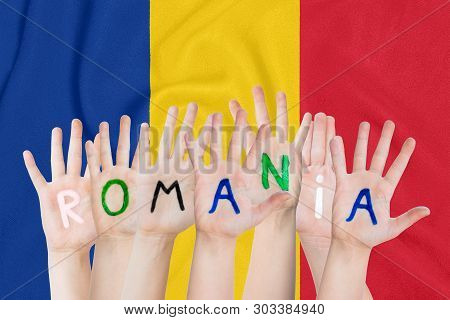 Inscription Romania On The Children's Hands Against The Background Of A Waving Flag Of The Romania