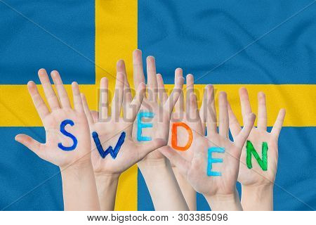 Inscription Sweden On The Children's Hands Against The Background Of A Waving Flag Of The Sweden