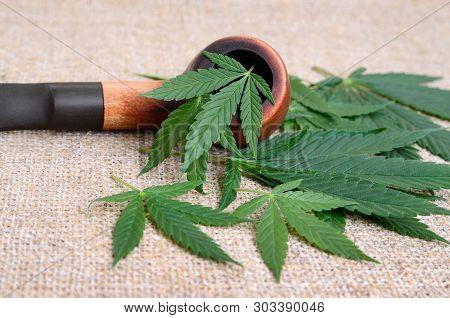 Smoking Pipe And Cannabis Leaves. Smoking Mix Of Marijuana, Medicine And Recreational Drug.