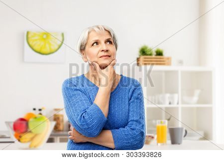 old people and decision making concept - portrait of senior woman in blue sweater thinking over kitchen background