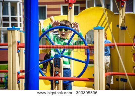 Boy As A Captain Or Sailors Play On The Ship Outdoors On Sunny Day. Kid Has A Lot Of Fun. Ship Has C