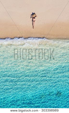 Aerial View Of A Girl On The Beach. Vacation And Adventure. Beach And Turquoise Water. Top View From