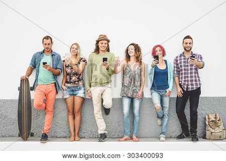 Group Of Friends Watching On Their Smart Mobile Phones Outdoor - Young Millennial People Having Fun