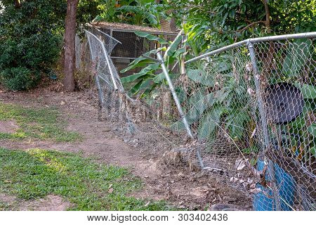 A Wire Mesh Fence Damaged By Flood Waters And A Build Up Of Debris