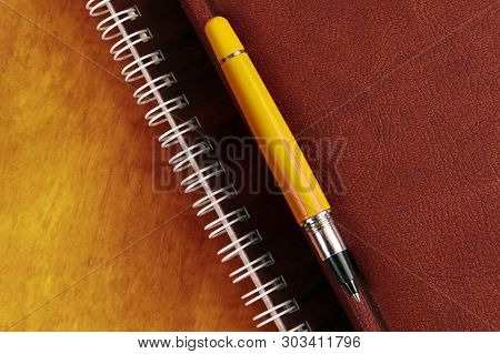 The Notebook And A Red Pen Lying On Wooden Desk. Items For Office And Education