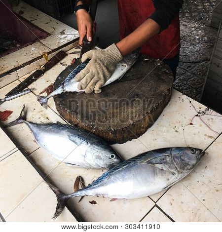 Hands In Gloves Of A Man Cleaning And Cutting A Tuna Fish On A Table With Two Fish Aside/fish Market