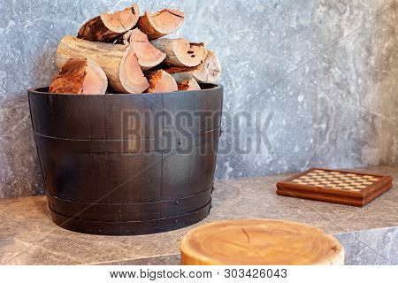A Barrel Full Of Chopped Logs Beside A Fireplace To Give Warmth From The Approaching Chill Of Winter