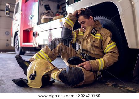 Photo of tired fireman sitting on floor near fire truck