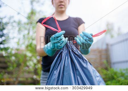 Image of woman in rubber gloves with full garbage bag on garden