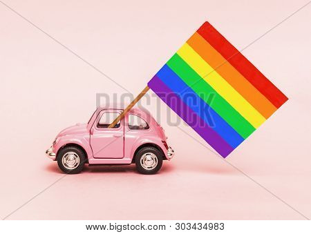 Pink Retro Toy Car Delivering Bright Rainbow Gay Flag On Soft Pink Backgraund. Concept Of Gay Parade