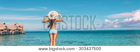 Beach summer travel vacation banner panorama woman in swimsuit and hat over blue ocean sky copy space with overwater bungalows hotels in the background.