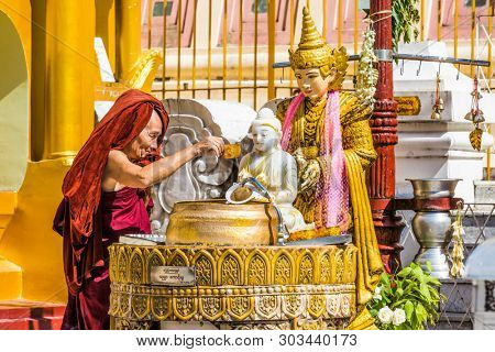 Yangon, Myanmar - December 16, 2016 : buddhist monk watering buddha statue at Shwedagon Pagoda Yangon in Myanmar