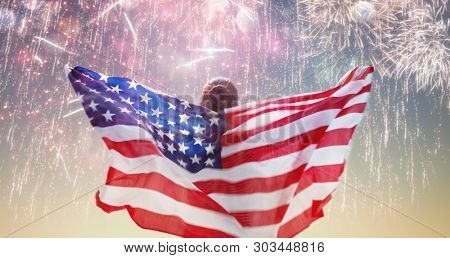 Patriotic holiday. Happy young woman with American flag looking at fireworks. USA celebrate 4th of July.