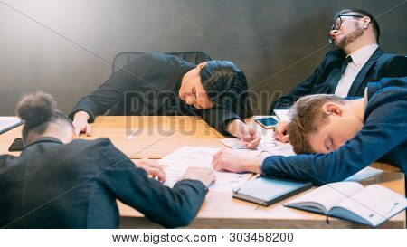 Overtime Work And Deadlines. Exhausted Professional Team. Young Business People Taking Nap In Confer