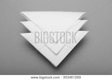 White Folded Paper Serviette, Bar Napkin. Gray Background