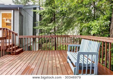 Back Of The House Deck With Blue Bench.