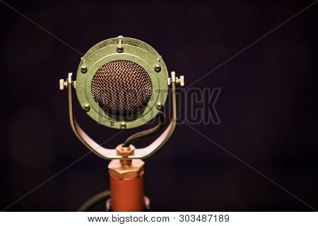 An Old Type Of Microphone On The Stage Against The Backdrop Of The Auditorium. Close-up Of Retro Mic