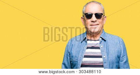 Handsome senior man wearing denim jacket and sunglasses with serious expression on face. Simple and natural looking at the camera.