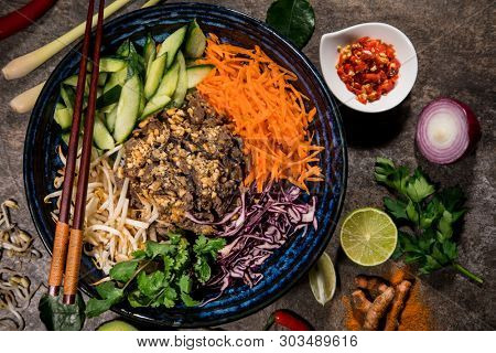 Bun bo nam bo asian food background with various ingredients on rustic stone background , top view. Vietnam or Thai cuisine.
