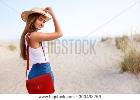 Stylish Woman Walks To The Beach In Straw Hat, Summer Denim Shorts And Red Fashionable Bag. Attracti