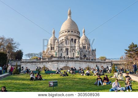 Paris, France - April 12, 2019 : People Sitting On The Grass In Front Of The Basilica Of The Sacre C