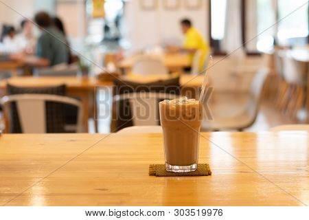 Ice Coffee In Glass, Placed On A Wooden Table In A Coffee Shop. The Customers Sit In The Cafe Blurre