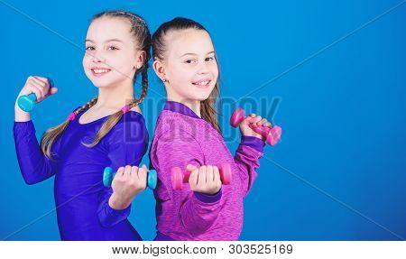 On way to stronger body. Girls exercising with dumbbells. Beginner dumbbells exercises. Sporty upbringing. Children hold dumbbells blue background. Sport for teens. Easy exercises with dumbbell poster