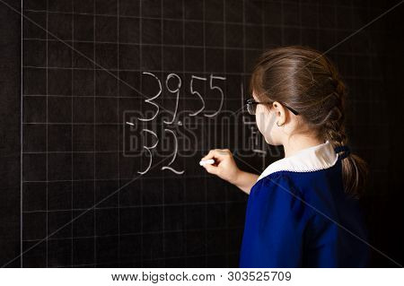 Italian Elementary School Girl Trying To Solve A Mathematics Examples, Making A Long Division At Bla