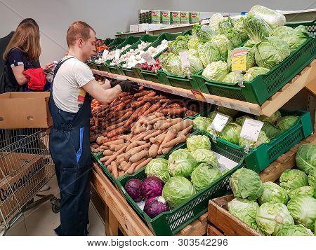 Minsk, Belarus - May 22, 2019: Worker Taking A Vegetables In Supermarket