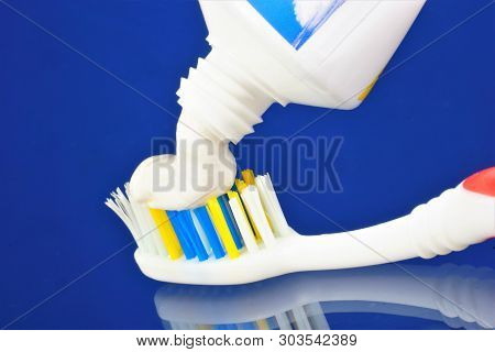 Toothbrush And A Tube Of Toothpaste On A Blue Background. Oral Hygiene Products - Toothbrush -- A De