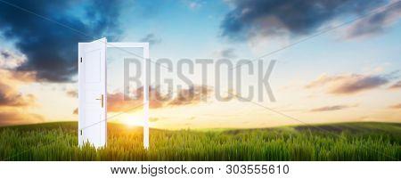 Open door on green grass. Concept of hope, new life etc. Sunset sky