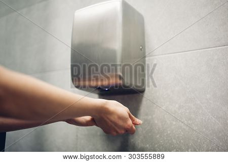 Air Dryer In Public Toilet. Woman Drying Hands In Water Closet.