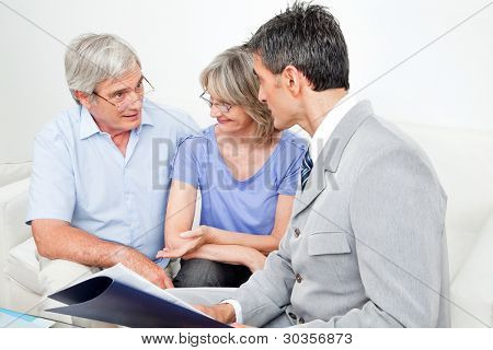 Investment consultant talking to senior couple at home in living room