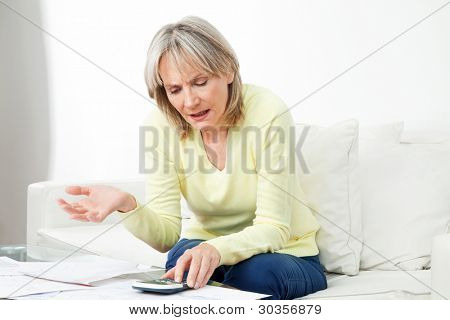 Frustrated senior woman with paperwork and calculator at home