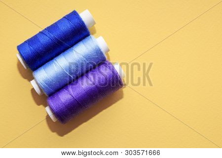 Concept For Needlework, Stiching, Embroidery. Sewing Multicolored Threads On Yellow Background. Top