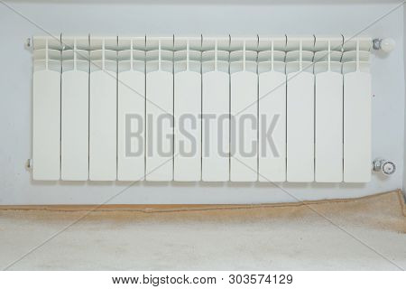 Just Installed A New Steel Heating Radiator. Full View Of A White Radiator Against A Cream Wall . In